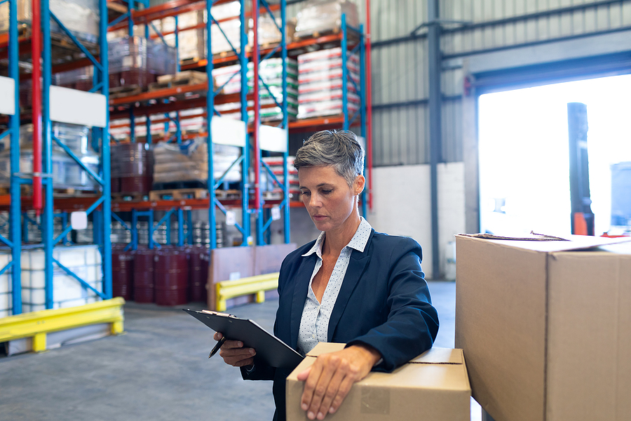 Manager checking supply chain stocks inside a warehouse